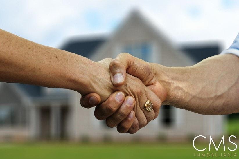 Agente inmobiliario estrechando la mano con un cliente.